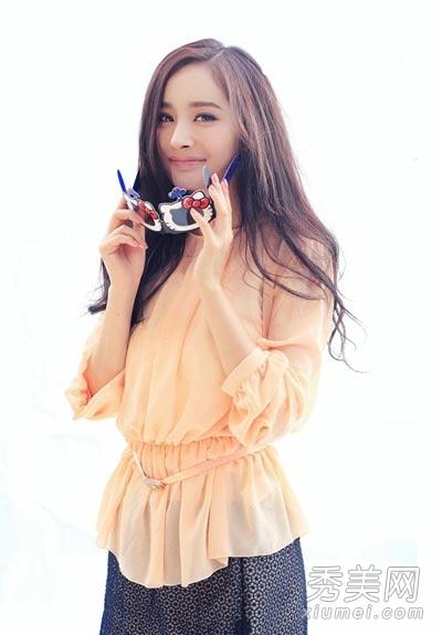 穿着浅黄色的宽松上衣搭配复古的雪纺半身长裙,甜美可爱的风格,杨幂